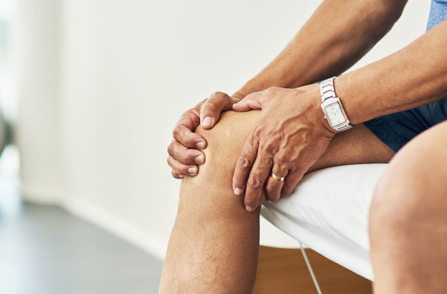 Older man with knee pain in doctor's office
