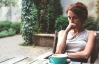 Woman sitting on porch and contemplating onset of early menopause