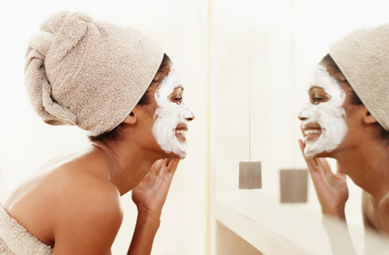 woman applying face mask in bathroom mirror