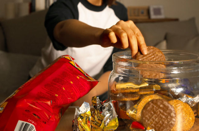 woman snacking on lots of chips and cookies