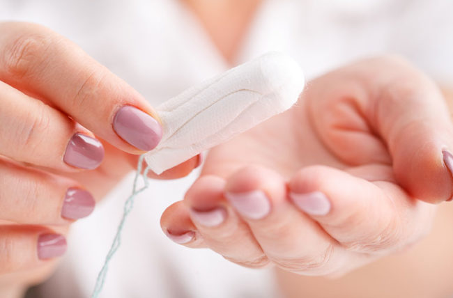 Woman's hands holding clean cotton tampon