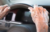 Elderly woman driving car with arthritic hands
