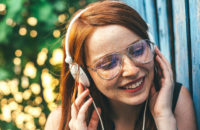 Young woman with freckles listening to music