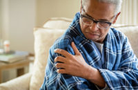 Older man rising from bed with shoulder pain