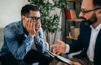 Young man during office visit with his psychiatrist discussing care