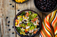 Salad containing rice, black beans, corn, tomatoes and romaine