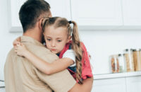 Daughter hugging dad after upsetting day at school