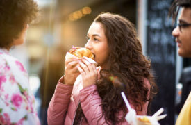 Young woman eating fast food chicken burger