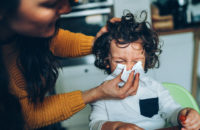 Mother wiping childs nose during cold season