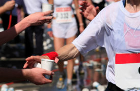 Athletes drinking water and electrolytes during a marathon