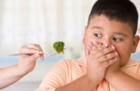 Young boy doesn't want to eat his broccoli