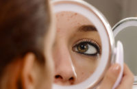 Woman using mirror to inspect pimples
