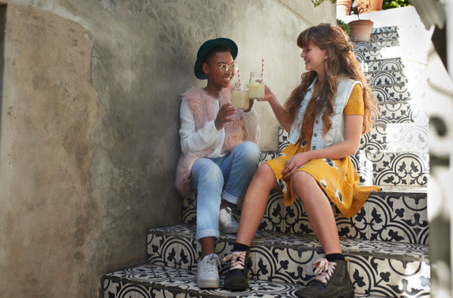 Two teen age girls drink lemonade on stairs