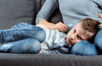 Small boy with upset stomach on couch with mother