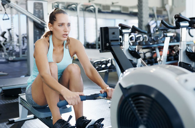 Woman on rowing machine as part of her interval training