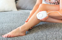 Woman using at-home laser hair removal on leg