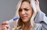 Woman is surprised and confused by positive pregnancy test
