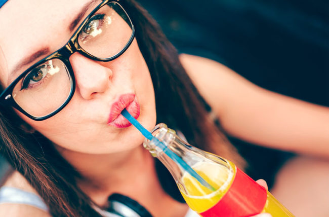 Young woman sipping soda through a straw