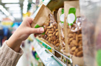 Hand with packaging of almonds in store