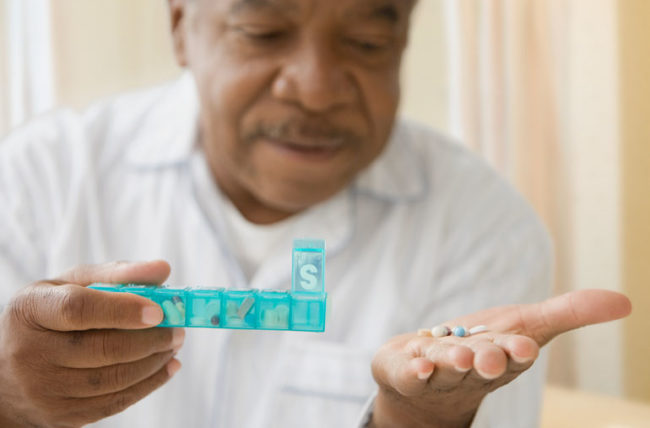 Elderly man taking his daily medications