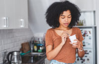 woman eating greek yogurt because of digestive disorder