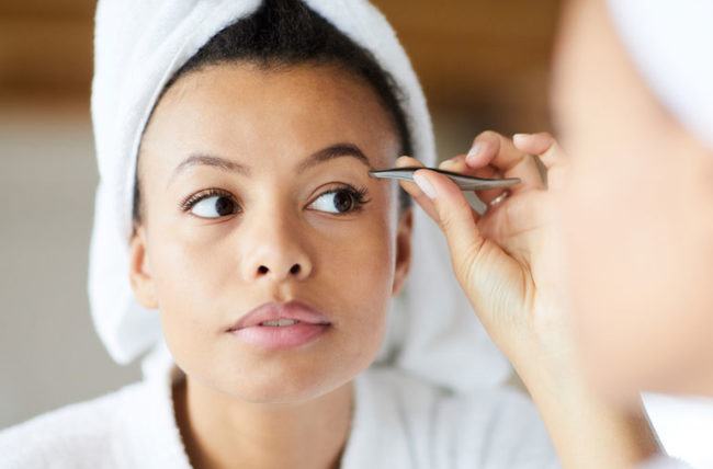 Woman is plucking her eyebrows after shower