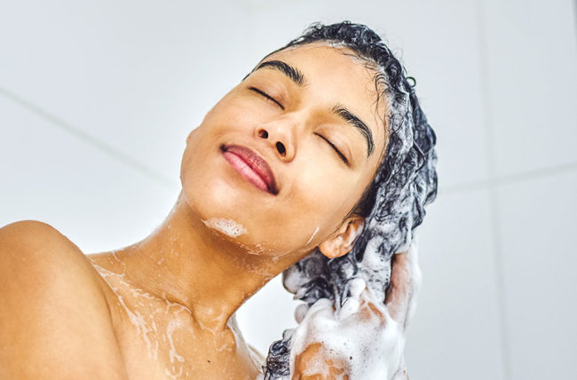 Woman washing her hair with enriching shampoo
