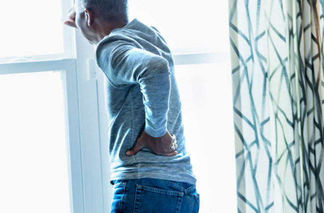 man with back pain looking out window