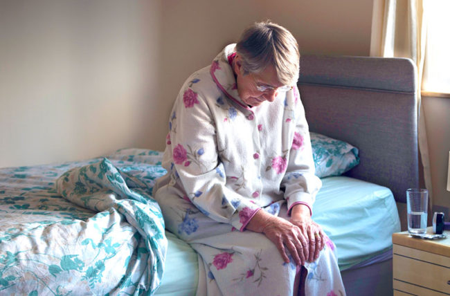 elderly woman sitting on bed experiencing aches and pains