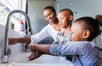 Mom and children wash hands at the sink