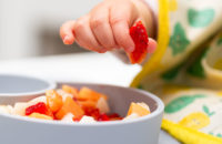 baby eating fruit that is cut up into small pieces
