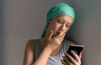 woman going through chemo tracking side effects on smartphone