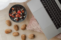 Snack of chocolate, strawberries and walnuts by laptop