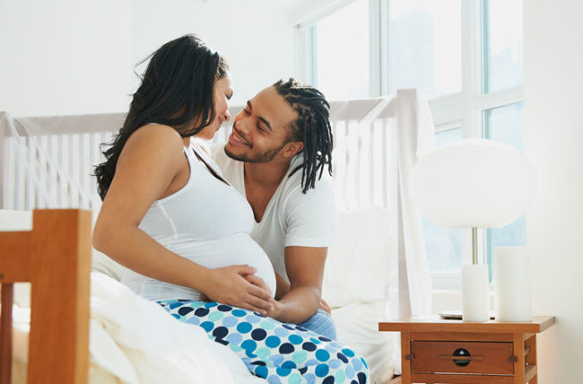 Pregnant woman and man cuddling in bed