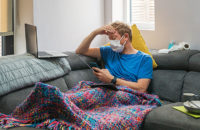 man with coronavirus holding head while on couch at home