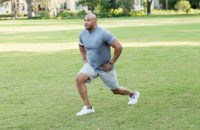 man dynamic stretching doing walking lunges