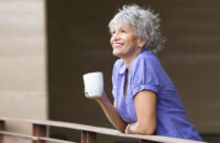 elderly woman standing on her balcony drinking coffee in the morning