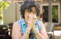 woman sneezing due to allergies