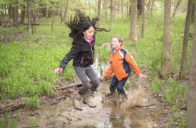 kids jumping in stream at park