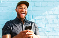 man laughing at text on smartphone