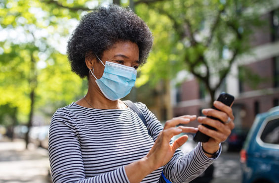 woman on street texting while wearing mask