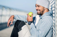 man on exercise break eating apple