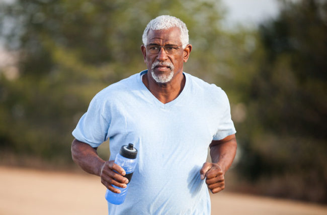 elderly man exercising with water in hand