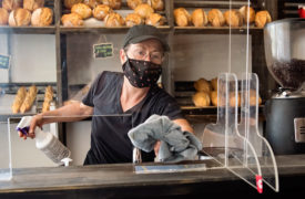 employee at bakery wearing a mask and working