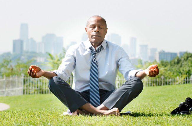 man meditating in the middle of a business day