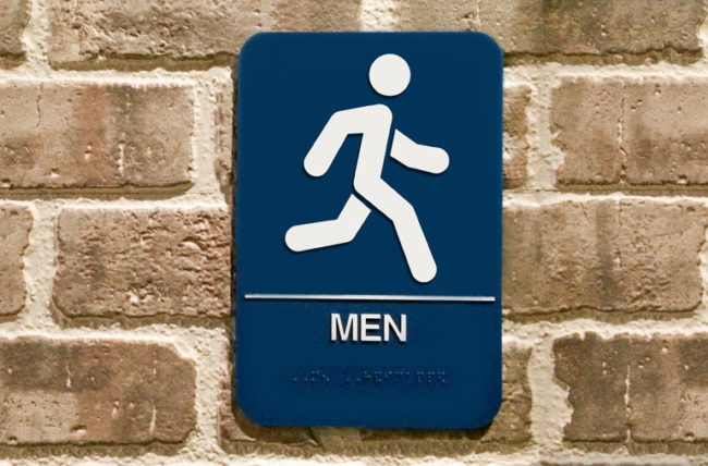 Bathroom sign with running man figure