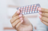 woman holding hormone therapy birth control pills