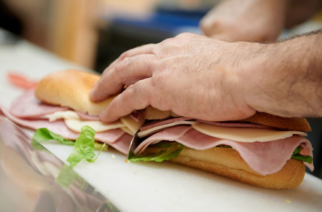 man cutting sub sandwich in half containing lunch meat and cheeses