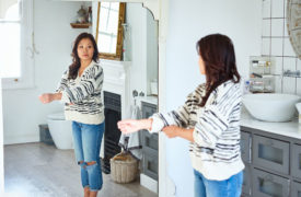 woman looking in mirror and not judging