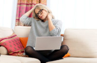 woman with headache while workingon laptop from couch